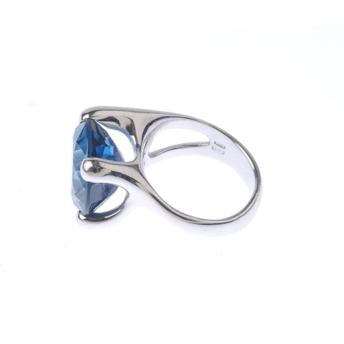 1291 - (547968-6-A) A topaz dress ring. The circular-shape blue topaz, with stylised and tapered band. Ital...