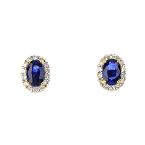 13 - A pair of 18ct gold sapphire and diamond cluster stud earrings. Each designed as an oval-shape sapph...