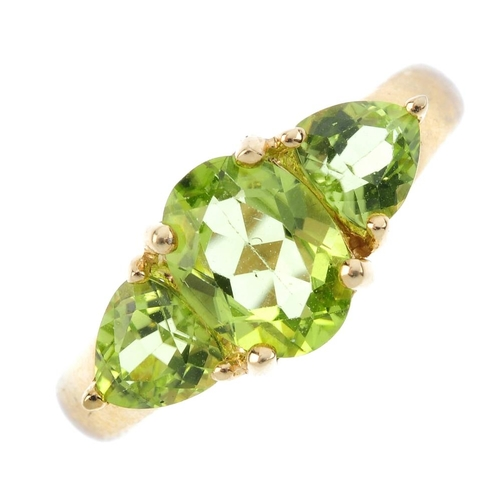130 - A 9ct gold peridot three-stone ring. The oval-shape peridot, with pear-shape peridot shoulders and t...