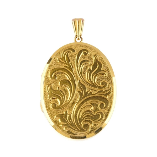 131 - A 9ct gold locket. Of oval-shape outline, the front with scrolling motif, suspended from a grooved s...