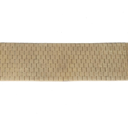 1312 - (549847-1-A) A 1970s 18ct gold bracelet. The textured brick-link wide bracelet, with engraved irregu...