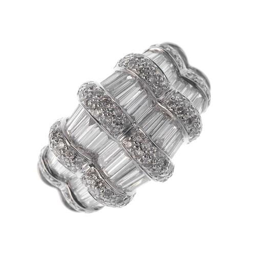 1316 - (550198-4-A) A diamond dress ring. The baguette-cut diamond line, with pave-set diamond line spacers...