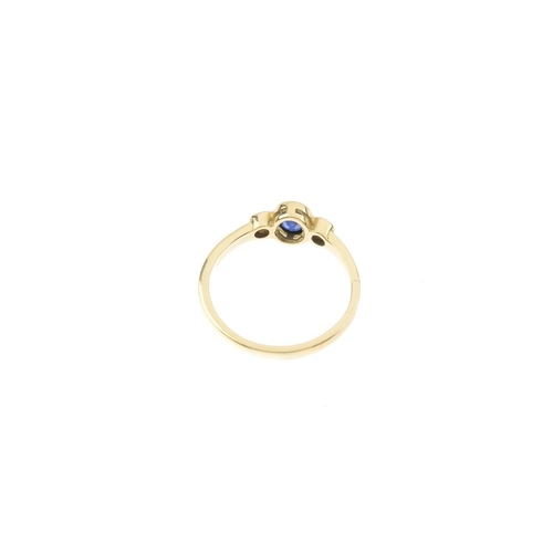 132 - An 18ct gold sapphire and diamond three-stone ring. The oval-shape sapphire collet, with brilliant-c...