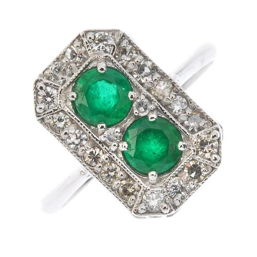 133 - An emerald and diamond dress ring. Of rectangular outline, the circular-shape emerald duo, within a ...