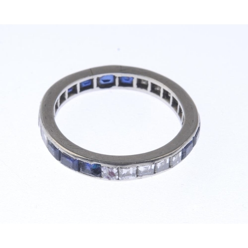 1347 - (7000808-3-A) A diamond and sapphire full-circle eternity ring. Comprising alternating square-shape ...