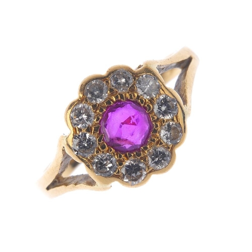1348 - (7000808-4-A) A ruby and diamond cluster ring. The circular-shape ruby, with brilliant-cut diamond s...