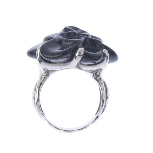 1356 - (203432) CHANEL - an 18ct gold 'Camelia' ceramic floral dress ring. The black ceramic flower, with o...
