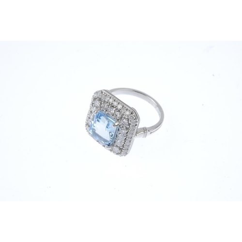 136 - An 18ct gold aquamarine and diamond cluster ring. The rectangular-shape aquamarine, within a brillia...