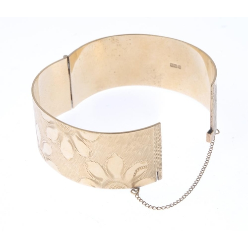 1363 - (72341) A 1960s 9ct gold hinged bangle. Of floral design the engraved flowers with a textured hinged...