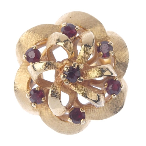 1364 - (72341) A mid 20th century garnet floral dress ring. Designed as a stylised openwork textured flower...