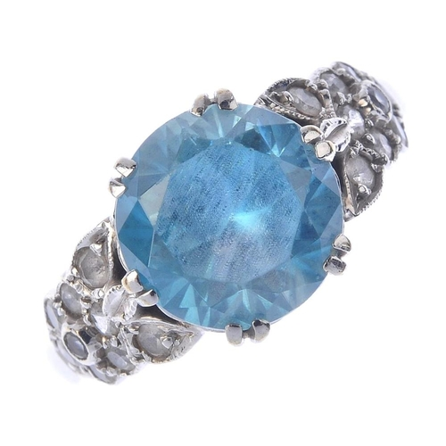 1365 - (72341) A mid 20th century zircon and gem-set ring. The circular-shape blue zircon, with colourless-...