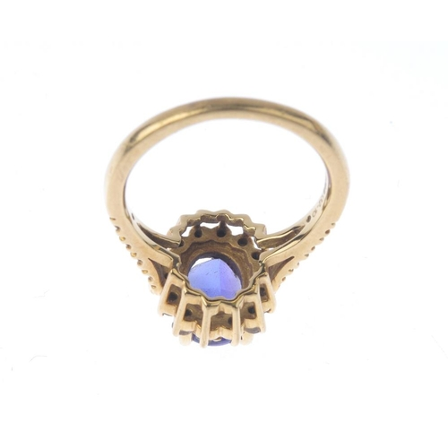 1370 - (133741) A 18ct gold diamond and coated gem-set cluster ring. The oval-shape coated gem, with a bril...