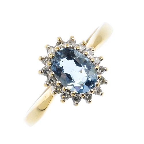 138 - An 18ct gold aquamarine and diamond cluster ring. The oval-shape aquamarine, with single-cut diamond...