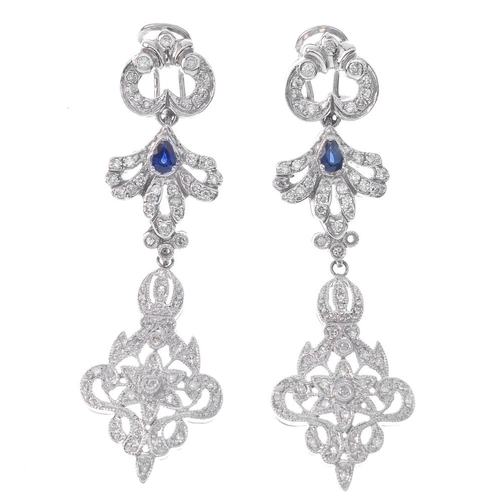 1380 - (203799) A pair of sapphire and diamond earrings. Each designed as a vari-cut diamond openwork folia...
