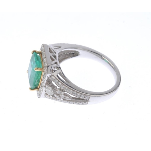 1385 - (203799) An emerald and diamond cluster ring. The square-shape emerald, with brilliant-cut diamond s...