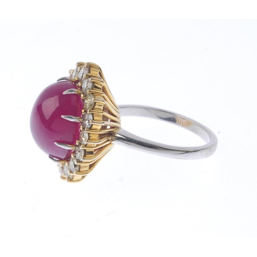 1387 - (203799) A ruby and diamond cluster ring. The oval ruby cabochon, with 'yellow' diamond and diamond ...