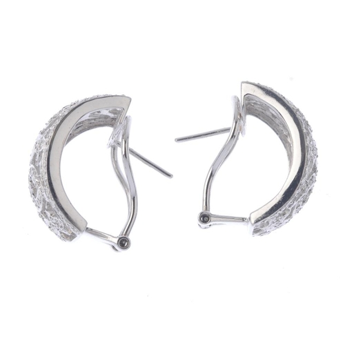 1391 - (203799) A pair of diamond earrings. Each designed as a brilliant-cut diamond openwork curved panel....