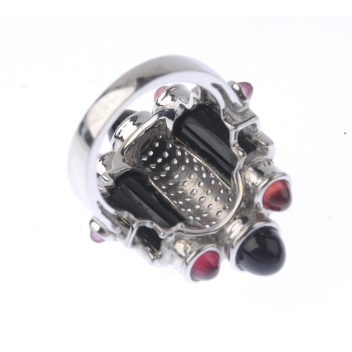 1394 - (201024) A gem-set dress ring. The pave-set diamond and onyx cylinders, with onyx and pink gem caboc...