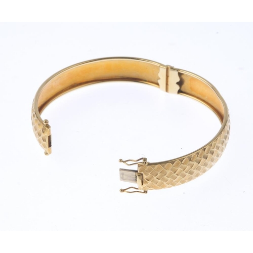 1396 - (63663) A bangle. The textured hinged bangle, with partially concealed push-piece clasp. Italian mar...