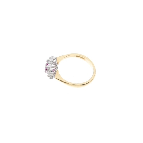 148 - An 18ct gold ruby and diamond dress ring. The oval-shape ruby, with brilliant-cut diamond trefoil sh...