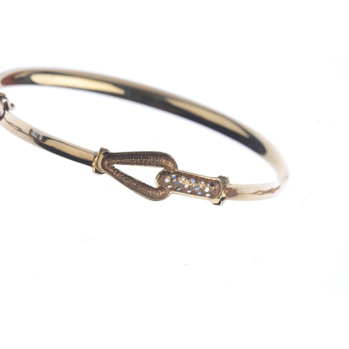 150 - Two 9ct gold hinged bangles. To include a sapphire and diamond bangle, together with an openwork pan...
