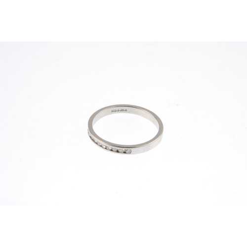 167 - A platinum diamond half-circle eternity ring. The brilliant-cut diamond line, within a channel setti...