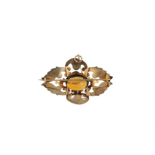 17 - A late Victorian citrine brooch, circa 1880. The oval-shape citrine, within an engraved foliate and ...