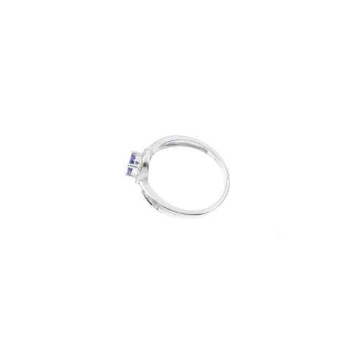 173 - A 9ct gold tanzanite and diamond cluster ring. The oval-shape tanzanite and single-cut diamond surro...