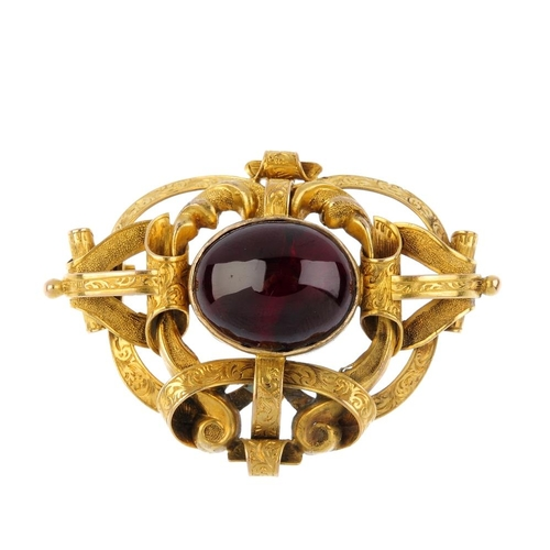 193 - A mid Victorian foil- backed garnet brooch. Of openwork design, The oval foil-backed garnet cabochon...