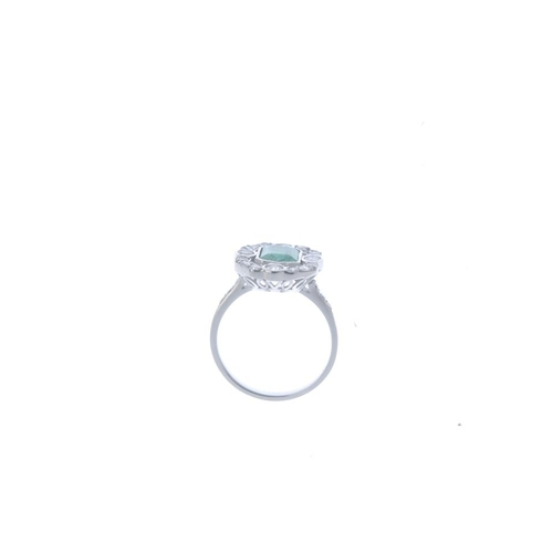 207 - An emerald and diamond cluster ring. The rectangular-shape emerald, with graduated brilliant-cut dia...