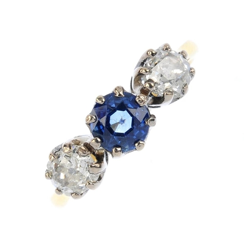 21 - An 18ct gold sapphire and diamond three-stone ring. The circular-shape sapphire, with old-cut diamon...
