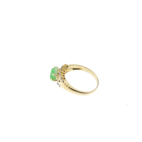 211 - A jade and diamond dress ring. The freeform jadeite cabochon, with brilliant-cut diamond sides and c...