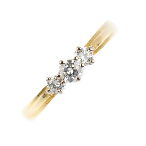 214 - An 18ct gold diamond three-stone ring. The brilliant-cut diamond line, with plain band. Total diamon...