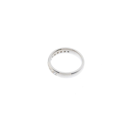 216 - A palladium diamond half-circle eternity ring. The brilliant-cut diamond line, to the plain band. Es...