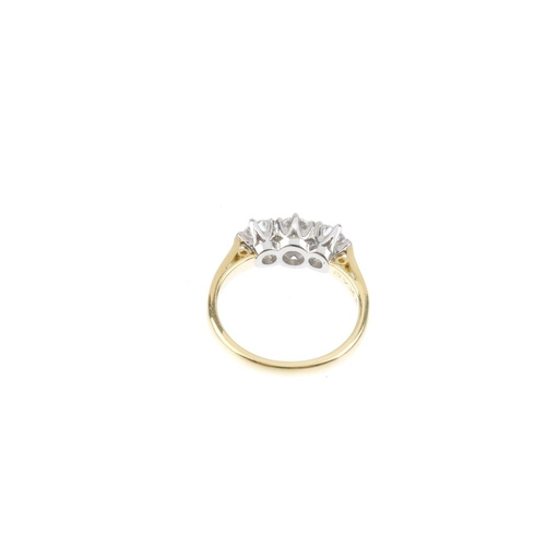 218 - An 18ct gold diamond three-stone ring. The graduated brilliant-cut diamond line, with bi-colour gall...