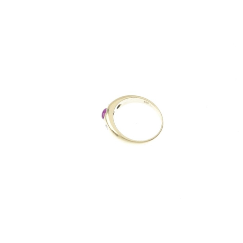 220 - A ruby and diamond ring. The oval ruby cabochon, with brilliant-cut diamond sides, inset to the tape...