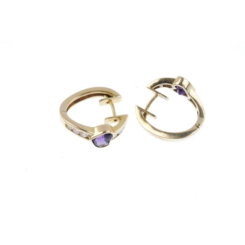24 - A pair of 14ct gold amethyst and diamond hoop earrings. Each designed as a heart-shape amethyst coll...