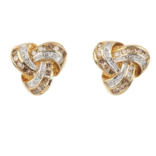 244 - A pair of 9ct gold diamond earrings. Each designed as a stylised knot, set with brilliant-cut 'brown...