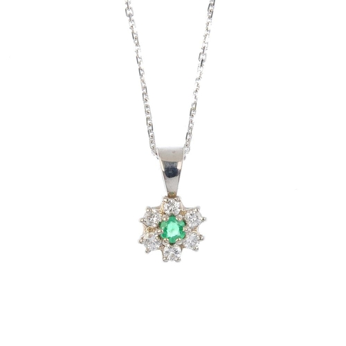 25 - An 18ct gold emerald and diamond pendant. The circular-shape emerald, with brilliant-cut diamond sur...