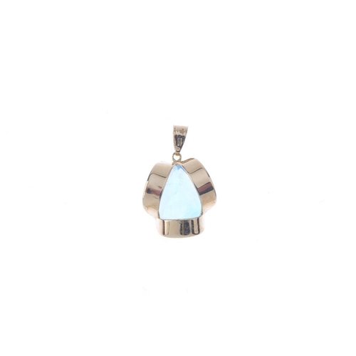 251 - A set of topaz jewellery. The 9ct gold pendant designed as a pear-shape blue topaz within a undulati...