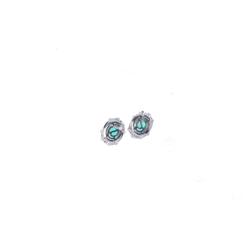 252 - A pair of emerald and diamond cluster earrings. Each designed as an oval-shape emerald, within a bri...