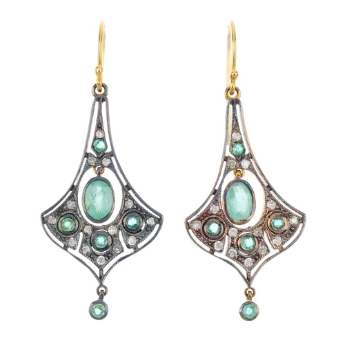 257 - A pair of emerald and diamond earrings. Each designed as an oval-shape emerald collet, within a circ...