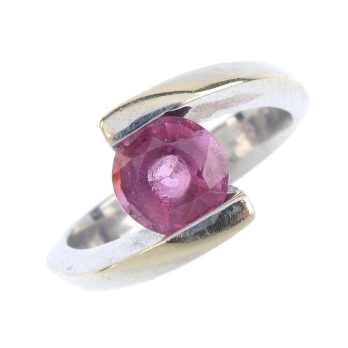 258 - A spinel and gem-set crossover ring. The circular-shape pink spinel, with pink-gem crossover shoulde...