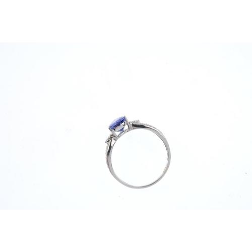 26 - An 18ct gold tanzanite and diamond ring. The pear-shape tanzanite, with brilliant-cut diamond trefoi...