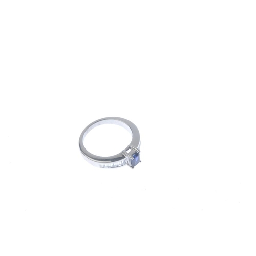 262 - An 18ct gold sapphire and diamond ring. The rectangular-shape sapphire, with graduated baguette-cut ...