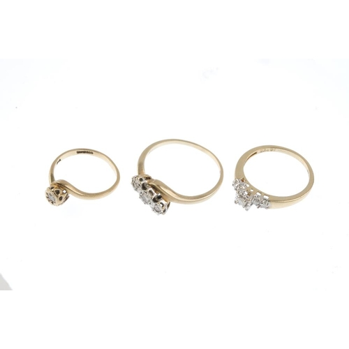 273 - Three 9ct gold diamond dress rings. To include a diamond three-stone ring with scrolling shoulders, ...
