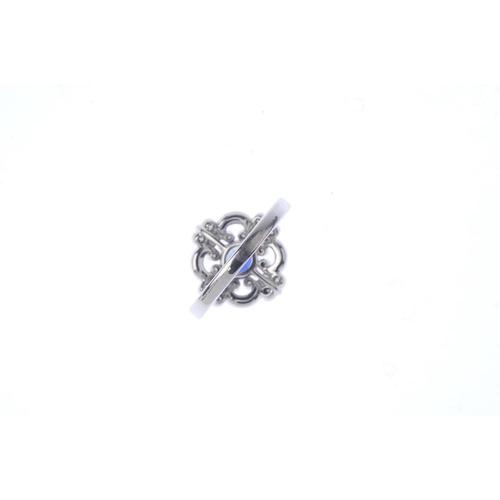 294 - An 18ct gold sapphire and diamond dress ring. The circular-shape sapphire, within a brilliant-cut di...