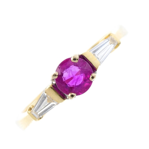 297 - An 18ct gold ruby and diamond three-stone ring. The circular-shape ruby, with tapered baguette-cut d...