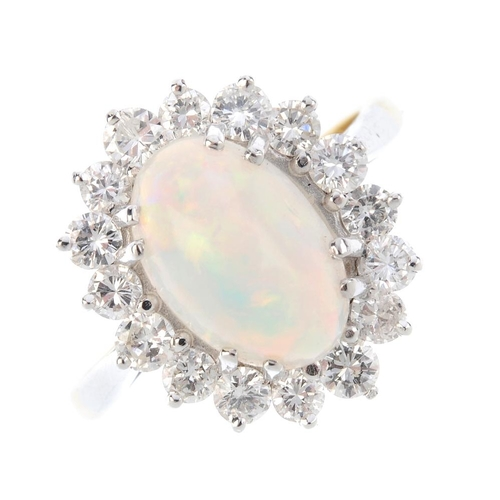 298 - An opal and diamond cluster ring. The oval opal cabochon, within a brilliant-cut diamond surround. E...