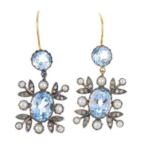 304 - A pair of topaz, split pearl and diamond earrings. Each designed as an oval-shape blue topaz, within...